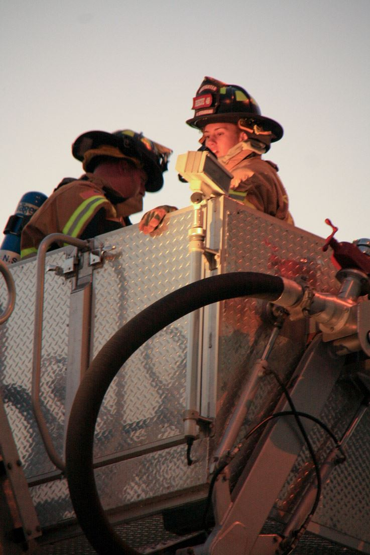 Two Firefighters on Top of the Fire Truck