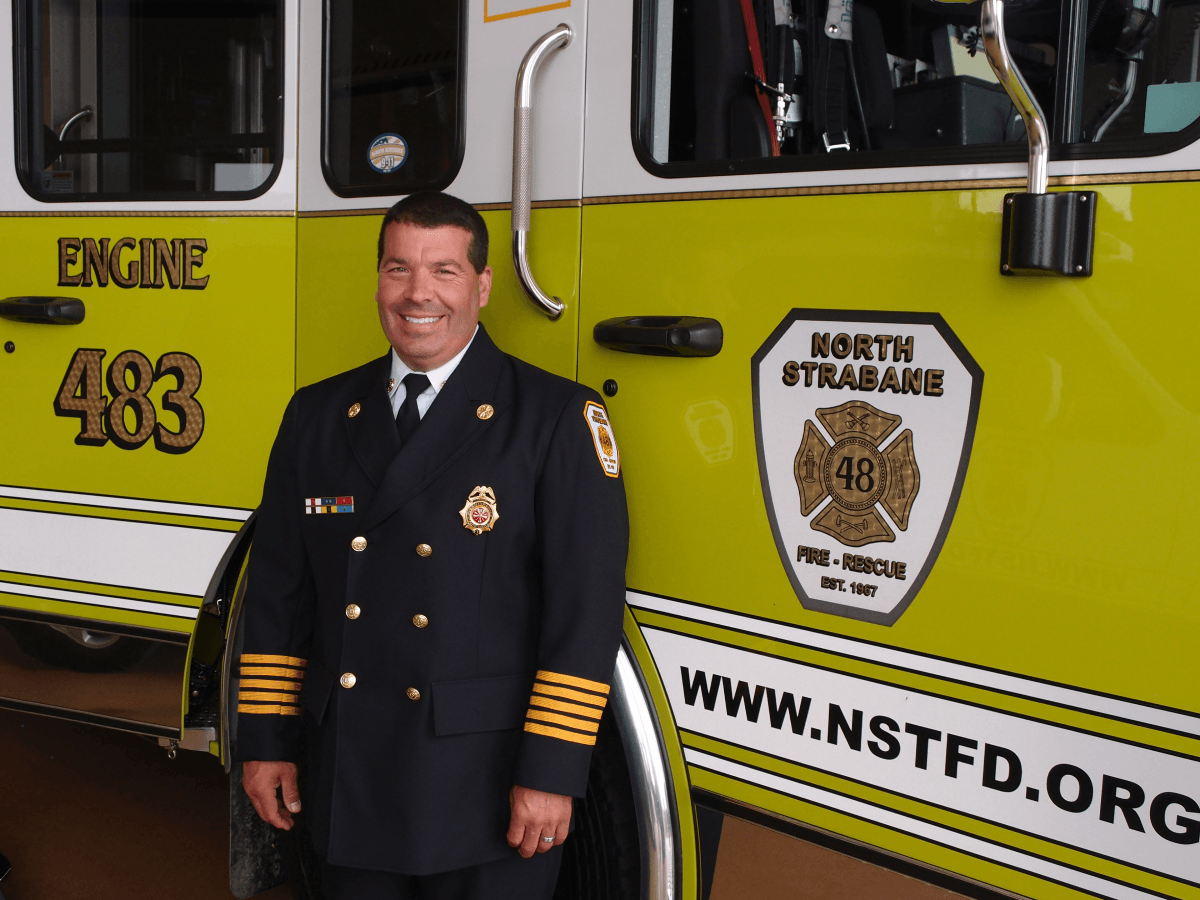 Fire Chief Mark Grimm in his Class a Uniform standing in front of a Pumper Truck